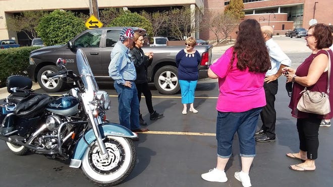 U.S. Rep. Tim Walberg (far left) and his wife, Sue, talk with Paul and Marilyn Hrivnak of Carleton (far right) and other visitors to a Catholics for Trump rally Sunday in a parking lot across from the Monroe County Courthouse and Monroe City Hall. In the foreground is a Harley-Davidson motorcycle that the Walbergs rode to the rally.