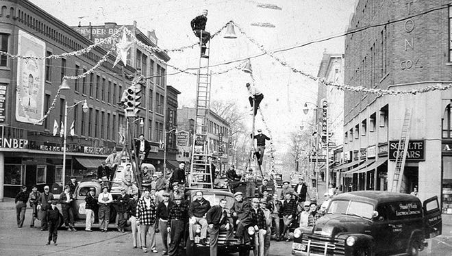 Men pause while putting up Christmas decorations in downtown Elmira in this photo, circa 1955.