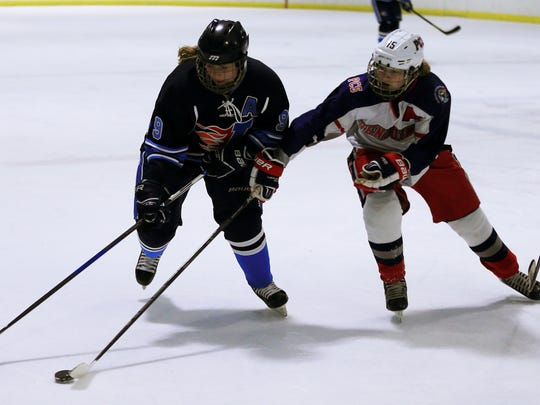 Livonia Ladywood's Devon Kelly (9) and Cathryn VandenBosch of the PCS Penguins battle for a loose puck during Tuesday's contest at Arctic Edge.