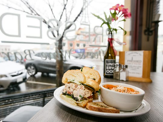 The cashew chicken sandwich, accompanied by a tomato cheddar soup, is served at Pressed Wine Bar in Dallas. (An earlier version of this photo information incorrectly identified the type of sandwich.)