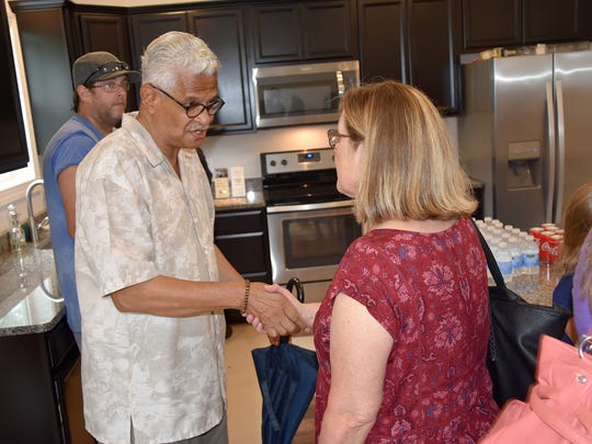 Melvyn Bantum meets his new neighbor, Susan Sartin, on Tuesday during a ribbon-cutting event for two homes in central Dover constructed by NCALL as part of the Restoring Central Dover initiative. The event took place at the North Queen Street home. Sartin purchased a home on Governors Avenue.
