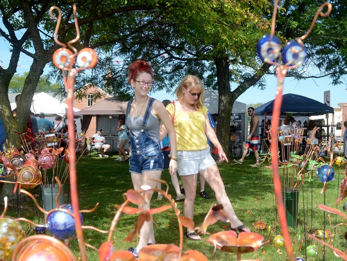 Ericka Goodman, left, 17, checks out lawn ornaments with her mother, Mary Goodman, of Lexington, KY, Sun, Aug 31, during the Algonac Art Fair.