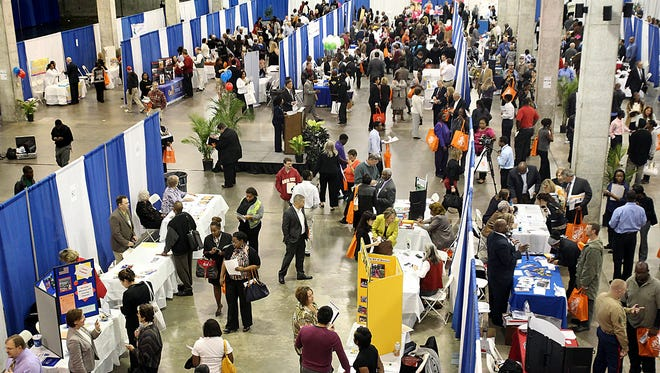 Job seekers browse employer exhibits at a job fa at the Civic Center.