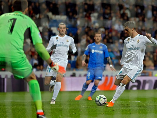 Real Madrid's Cristiano Ronaldo, right, attempts a shoot against Getafe's goalkeeper Emiliano Martinez during the Spanish La Liga soccer match between Real Madrid and Getafe at the Santiago Bernabeu stadium in Madrid, Saturday, March 3, 2018. (AP Photo/Francisco Seco)