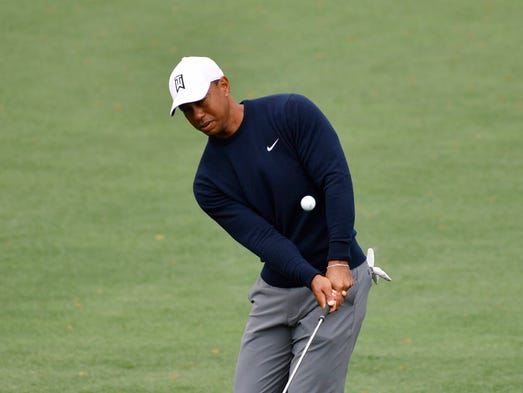 Tiger Woods chips onto the 2nd green during a practice