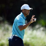 iger Woods shows his ball to the gallery after putting on the 14th green during the second round of The Players Championship golf tournament at TPC Sawgrass - Stadium Course.