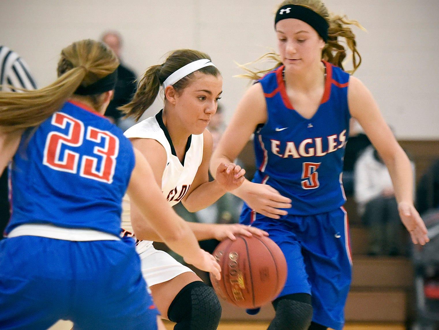 Tech's Mara Weaver takes the ball between Apollo's Calli Lynch, left, and Ashley Koepp during the first half Tuesday, Dec. 8 at Apollo High School.