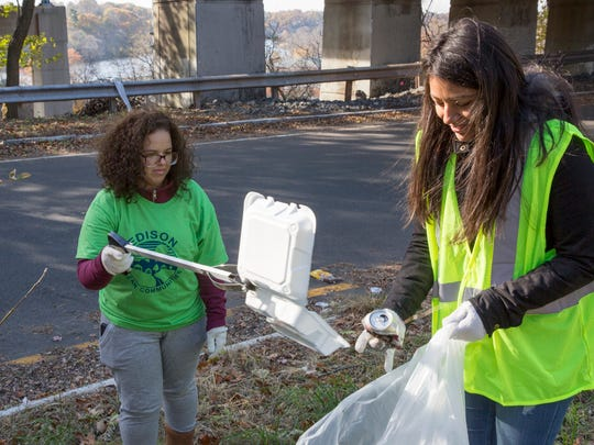 Middlesex County College students in Professor Alexandra Fields' Integrated Reading and Writing course recently partnered with the Edison Township Environmental Commission and the Lower Raritan Watershed Partnership to carry out a community cleanup at the Fox Road underpass in Edison. Students have spent this semester studying various environmental issues, and used their reading and writing skills to plan and promote the cleanup. Students collected 17 bags of trash and recyclables, along with nine tires, a suitcase, car seats, and various other large trash items. Here, Jessica Colon of Rahway, left) places some trash in the bag held by Carolyn Muncibay of Old Bridge.