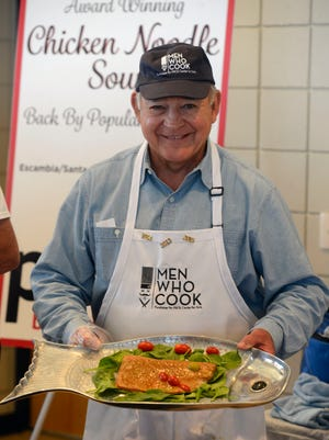 Chef Dick Bedics shows off his smoked salmon on a bed of spinach during a past Men Who Cook charity event to benefit PACE Center for Girls.