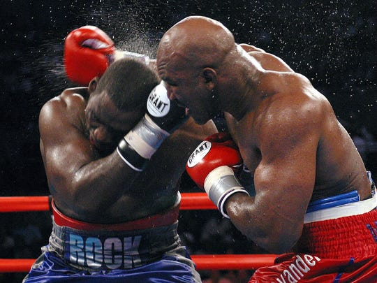 Evander Holyfield (right) lands a punch to the head