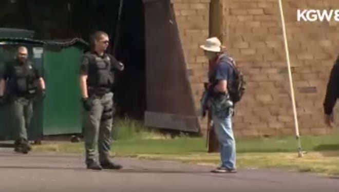 In this screengrab from KGW-TV video, a Marion County (Ore.) Sheriff's Deputy is seen talking to Kevin Straw in Detroit, Ore., on Monday, June 4, 2018. The video later captures deputies repeatedly punching Straw.