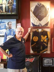 Bobby Plump stands next to a painted piece of the Milan Gym floor created for him to hang at his restaurant and bar, Plump's Last Shot, located in Broad Ripple Village, in Indianapolis.