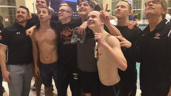 Members of the Cathedral Prep swimming and diving team celebrate the 2018-19 team state championship at the PIAA Class 2A meet at Bucknell University in Lewisburg.