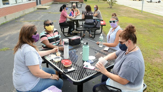 Sarah McCoy, left, Karon Ashe, Laura Laidley and Holly Gorman, all paraprofessionals at John B. Stanton Elementary School, enjoy lunch on one of several benches in front of the Norwich school Tuesday. The school will be getting up to 10 picnic tables that they will set up behind the school.