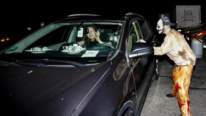 """Eliza Forman of Brighton hides behind Genevieve Bregoli of Milton who screams as she is surprised by an actor from the Barrett's Haunted Mansion's """"Screens and Screams"""" drive-in movie on Friday, Sept. 25, 2020 in Abington."""