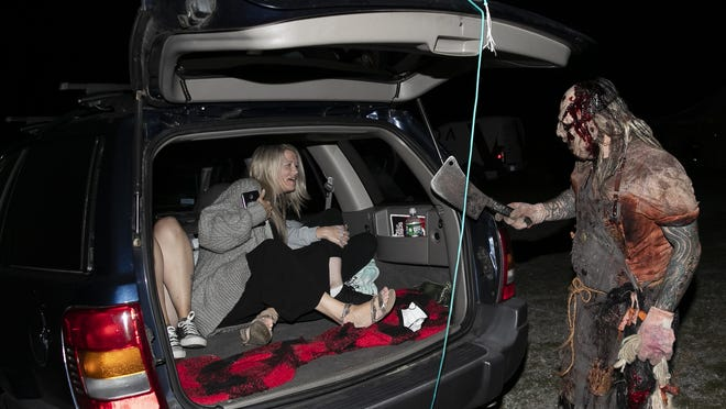 "Natalie Miller, 38, of Hanover jumps back as she and Sam Brennan, 32, of Rockland and Rebecca Wallis, 39, of Whitman are surprised by an actor from Barrett's Haunted Mansion during the"" Screens and Screams"" drive-in movie on Friday, Sept. 25, 2020 in Abington."