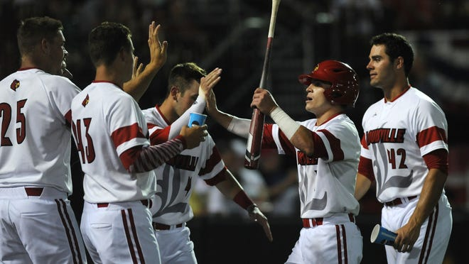 Sutton Whiting (holding the bat) and his U of L teammates celebrate an early run. The Cardinals scored five of them but needed only one.