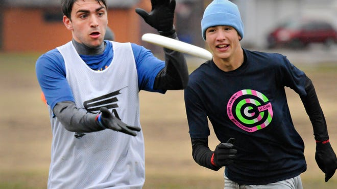 Charlie Schuweiler pulls in a pass in front of Owen Berg-Arnold during a scrimmage of the St. Cloud Cathedral Ultimate Frisbee team Wednesday in Centennial Park.