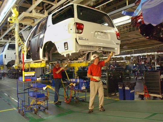 Toyota employees, David Wright, left, and James Eckerty add parts to vehicles on the assembly line in June of 2001.