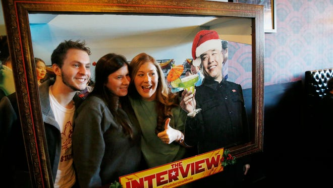 """From left, siblings William Abney, Katie Abney and Savannah Abney pose while their mother, Dee Abney, takes a photograph of them with an advertisement for the film """"The Interview"""" that is playing at the Alamo Drafthouse Cinema in Richardson, Texas, Thursday, Dec. 25, 2014. The film's Christmas Day release was canceled by Sony after threats of violence by hackers linked to North Korea, but the release was reinstated in some independent theaters and through a variety of digital platforms."""