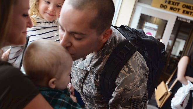 Vermont Air National Guard Staff Sgt. Dustin Chicoine of Georgia kisses his son Owen as he holds his daughter Addison after meeting them and his wife Tunie at Burlington International Airport on Monday, April 17, 2017, after leaving for a deployment in October, just weeks after Owen was born.