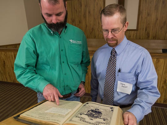 Jeremy Vincent and Dr. James Hassell look over the Kistler Bible that was found at First Baptist Church and presented to the WTBR during its 70th Anniversary celebration August 5, 2017.