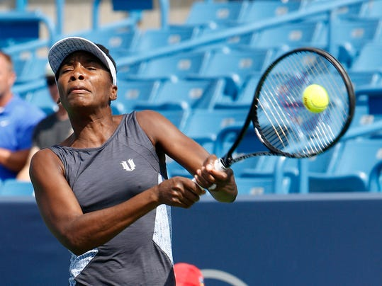 Venus Williams returns a volley to Lucie Safarova, from Czech Republic, during a first round match at the Western & Southern Open tennis tournament, Tuesday, Aug. 12, 2014, in Mason, Ohio. (AP Photo/David Kohl)