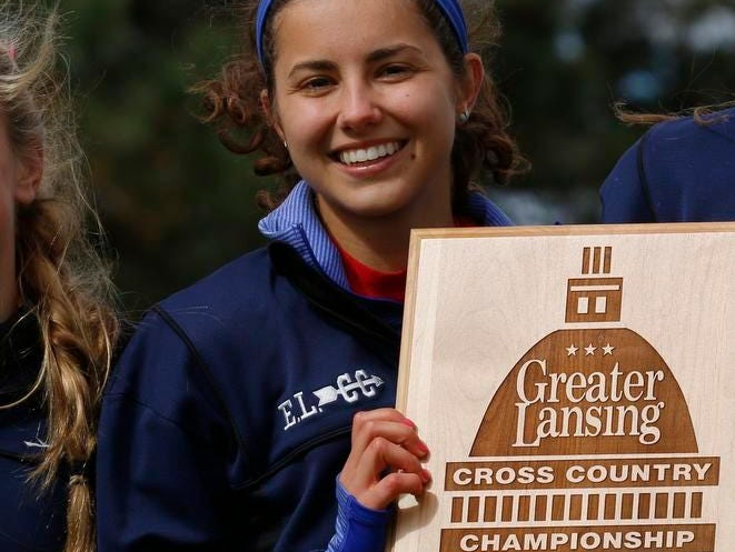 Stephanie Vanis, who placed 1st overall, stands with her East Lansing teammates who place 1st as a team in the Greater Lansing Cross Country Championship on Saturday in Grand Ledge.