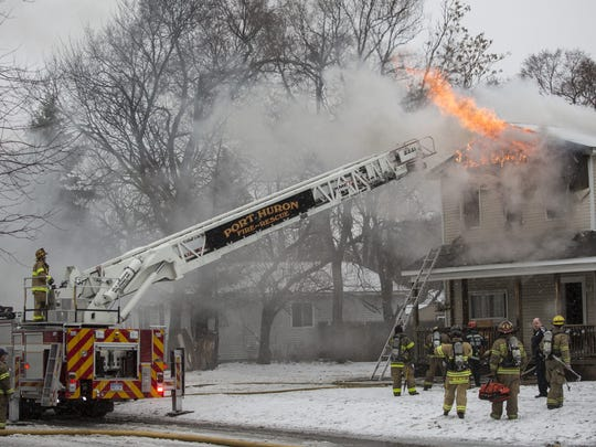 Members of the Port Huron Fire Department work the scene of a house fire in 2016 at the corner of 11th and Cedar streets.