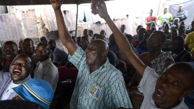 People react as partial results of the Nigerian presidential elections are released by the Independent National Electoral Commission.