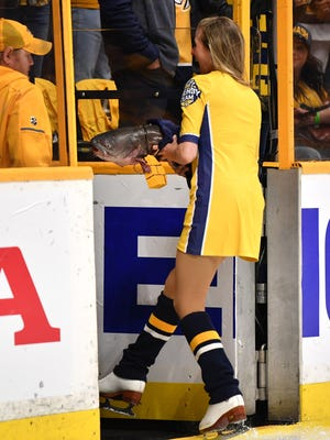 A member of the Predators Energy Team picks up a catfish before game 2 of the first round NHL Stanley Cup Playoffs at Bridgestone Arena Saturday, April 14, 2018, in Nashville, Tenn.