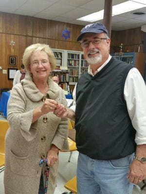 Andy Gartenberg, right, owner of Gartenberg Jewelry, presents a bracelet to Lucy Carty of Chambersburg.