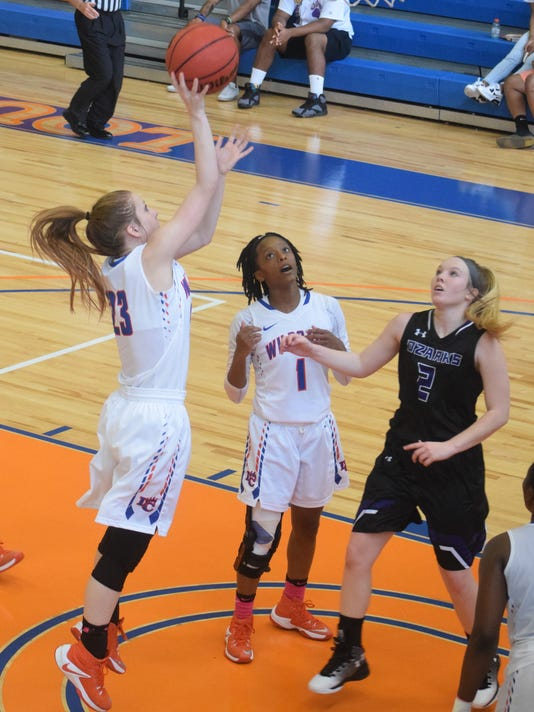 Louisiana College's Karlee Teddlie (23, far left) shoots two in the last seconds of the first half as teammate Kourtney McGhee (1, center) and the University of the Ozarks' Hailey Ostrander (2, far right) watch.