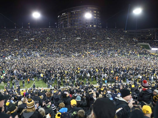 Nov 12, 2016; Iowa City, IA, USA; Fans storm the field after Iowa Hawkeyes place kicker Keith Duncan (not pictured) kicks the game winning field goal against the Michigan Wolverines at Kinnick Stadium. The Hawkeyes won 14-13.