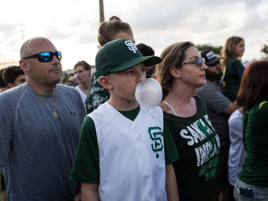 A young boy blows a bubble as he watches Santa Fe play