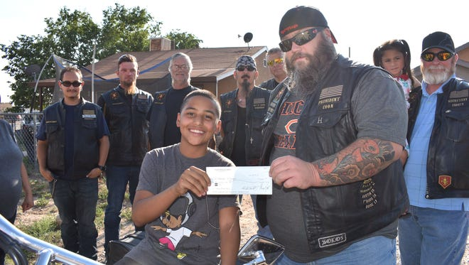 Pipe Hitters Union President Mike Tekell presents Nicholas Ellinger and his mom Maria Candelaria the money the motorcycle club raised to help with their costs from Nicholas's battle with cancer.