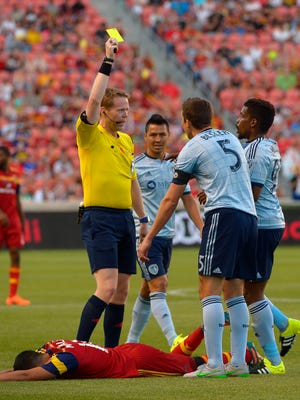 Real Salt Lake midfielder Javier Morales (11) is taken down by Sporting KC defender Matt Besler (5) who gets a yellow card on the play in a U.S. Open Cup soccer match Sunday, June 21, 2015, in Sandy, Utah. (Leah Hogsten /The Salt Lake Tribune via AP) DESERET NEWS OUT; LOCAL TELEVISION OUT; MAGS OUT