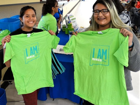 "Gadsden High School students Laura Romero and Alma Hernandez hold up their ""I am New Mexico True"" T-shirts."