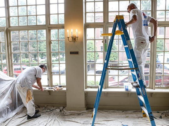Painters work on the window trim inside the current