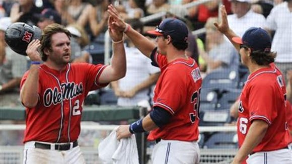 Ole Miss' Sikes Orvis is congratulated by teammates in the Rebels' win in the College World Series.
