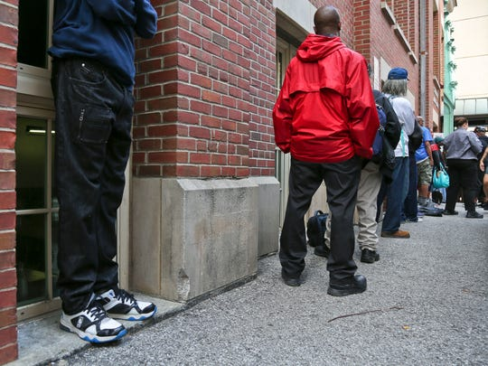 People wait in Cathedral Alley for the free lunch provided daily by the Cathedral of the Assumption on Tuesday afternoon. The city of Louisville plans to recognize the free meals of bologna sandwiches with a marker.