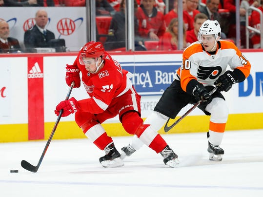 Detroit Red Wings center Dylan Larkin (71) protects the puck from Philadelphia Flyers center Jordan Weal (40) during the first period of an NHL hockey game Tuesday, March 20, 2018, in Detroit. (AP Photo/Paul Sancya)