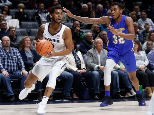 Xavier's Trevon Bluiett (5) eyes the basket against Morehead State's Djimon Henson (32) in the first half of an NCAA college basketball game, Friday, Nov. 10, 2017, in Cincinnati. (AP Photo/John Minchillo)