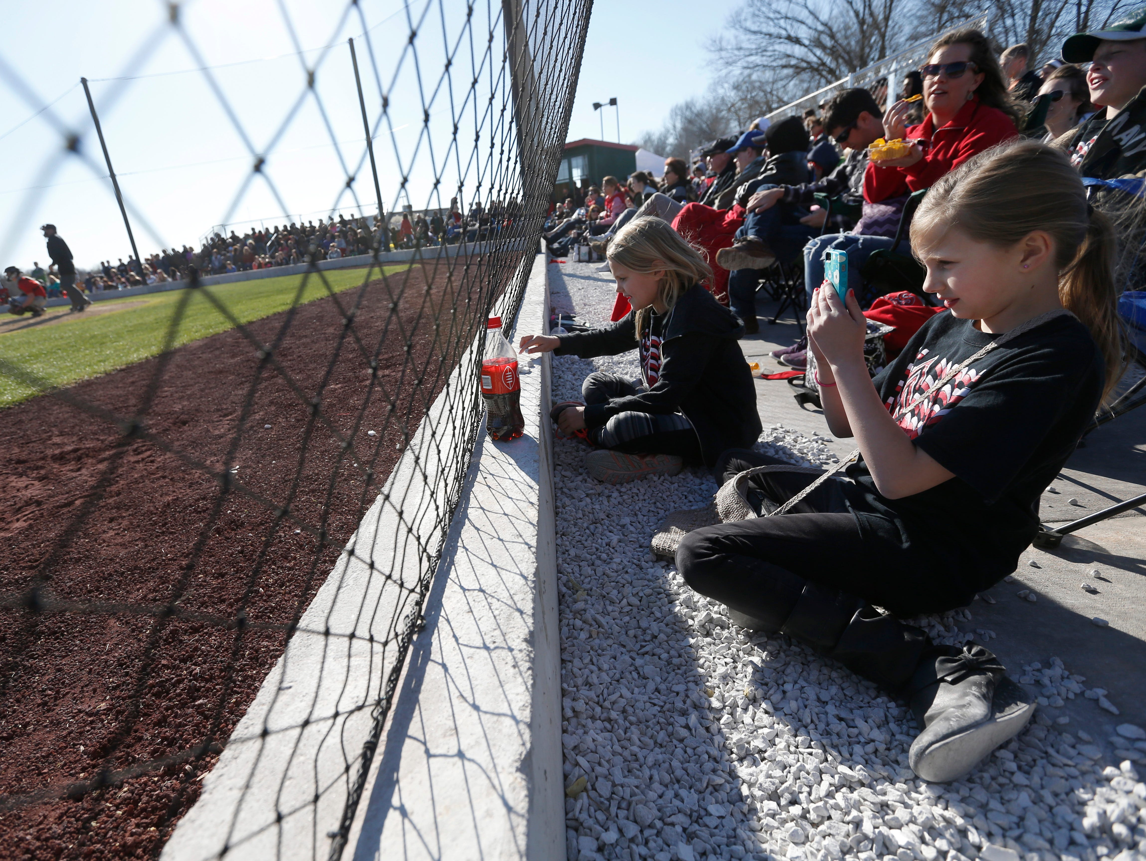 Noelle Germany, 10, right, takes a photo during the New Covenant Academy Warriors baseball team's first game at Federal Protection Field on Monday, Mar. 21, 2016.