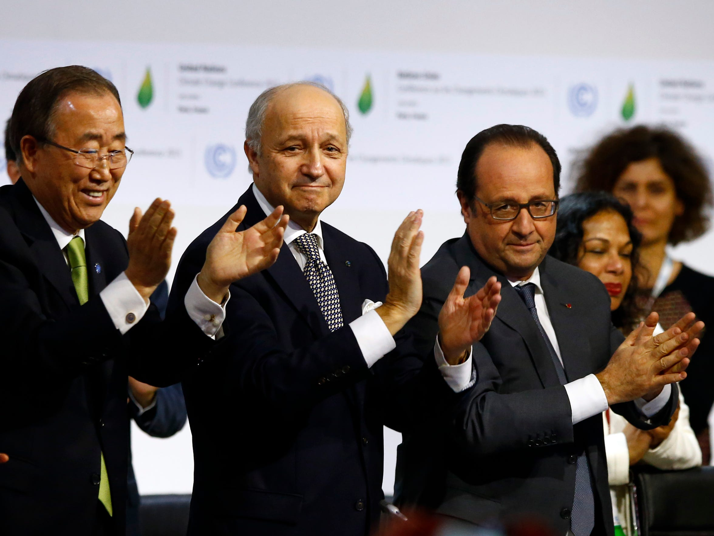 United Nations Secretary General Ban Ki-moon, left, French Foreign Minister Laurent Fabius, center, and French President Francois Hollande applaud at the end of the United Nations climate summit at Le Bourget, north of Paris, on Dec.12, 2015.