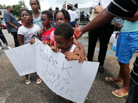 "Children hold signs reading ""Black Lives Matter"" outside the Triple S convenience store where Alton Sterling was killed in Baton Rouge, La., July 6, 2016."