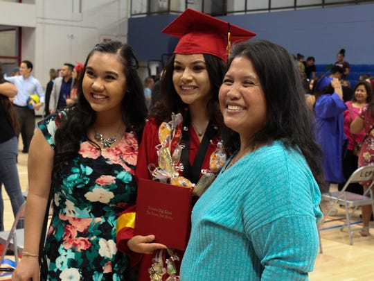 Annie Acosta, who graduated from Centennial High School, poses with family members and her diploma following the 2018 Las Cruces Public Schools summer commencement ceremony.