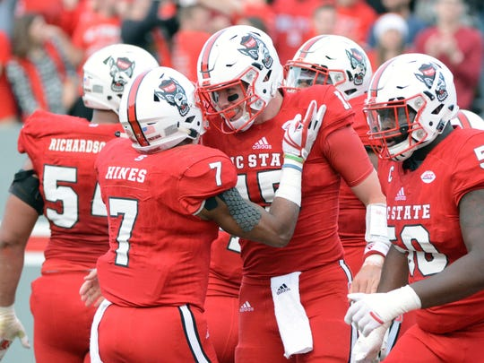 North Carolina State Wolfpack quarterback Ryan Finley (15) celebrates a touchdown with teammate Nyheim Hines (7) during the first half against the North Carolina Tar Heels at Carter-Finley Stadium.