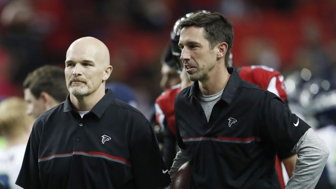 Atlanta Falcons Offensive Coordinator Kyle Shanahan, right, speaks with Atlanta Falcons head coach Dan Quinn before the first half of an NFL football NFC divisional playoff game between the Atlanta Falcons and the Seattle Seahawks, Saturday, Jan. 14, 2017, in Atlanta.