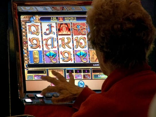 A woman plays the Cleopatra slot machine at the Golden